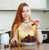 Smiling long-haired girl eating cherry Royalty Free Stock Images