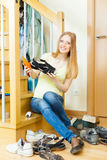 Smiling long-haired woman cleaning shoes Stock Photos