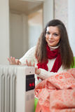 Smiling long-haired woman near heater Stock Image