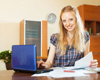Smiling long-haired woman working with  documents and laptop Royalty Free Stock Images