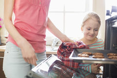 Smiling looking at mother removing cookie tray from oven at home Stock Photography