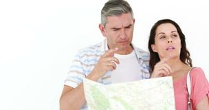 Smiling lost couple looking at map stock video