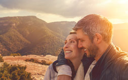 Smiling love with sunset. Couple in the top of the mountains stock image