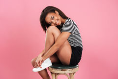 Smiling lovely african woman sitting and posing on a chair. Portrait of a smiling lovely african woman sitting and posing on a chair  over pink background Stock Photo