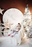 Smiling lovely baby girl in cute dress with lots of christmas presents. stock photography