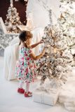 Smiling lovely baby girl in cute dress with lots of christmas presents. royalty free stock image
