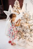 Smiling lovely baby girl in cute dress with lots of christmas presents. stock photos
