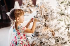 Smiling lovely baby girl in cute dress with lots of christmas presents. stock photo
