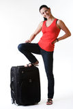 Happy young woman ready to travel. Smiling lovely brunette woman full-length standing next to her baggage- ready for her summer travel. Shot in studio. Isolated Royalty Free Stock Images