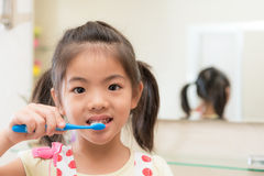 Smiling lovely children girl using toothbrush. Cleaning teeth and face looking at camera with mirror reflection image background in bathroom at home royalty free stock photos