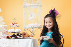 Smiling lovely girl drinking tea with sweet treats Royalty Free Stock Photography