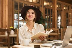 Smiling lovely girl in hat sitting at the cafe table indoors, reading a book royalty free stock image