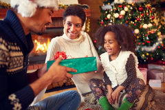 Smiling lovely girl receiving Christmas present from parents. Happy family near fireplace stock images