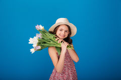 Smiling lovely little girl in hat holding bouquet of flowers Royalty Free Stock Photography