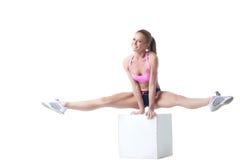 Smiling lovely sportswoman doing split on cube Royalty Free Stock Image
