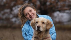 Smiling lovely woman with her dog in autumn nature stock footage