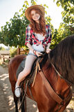 Smiling lovely young woman cowgirl riding horse Royalty Free Stock Photo