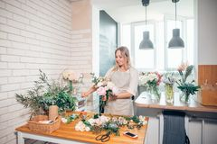 Florist workplace: woman arranging a bouquet with flowers. Smiling lovely young woman florist arranging plants in flower shop stock photos