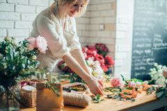 Florist workplace: woman arranging a bouquet with flowers. Smiling lovely young woman florist arranging plants in flower shop royalty free stock photo