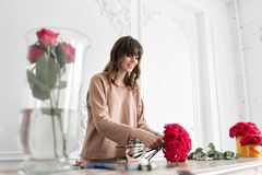 Smiling lovely young woman florist arranging plants in flower shop. People, business, sale and floristry concept. Bouquet of red roses stock photo
