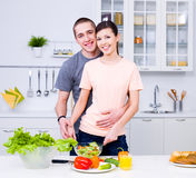 Smiling lovers cooking in the kitchen Royalty Free Stock Images