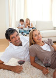 Smiling lovers drinking wine lying on the floor Stock Photography