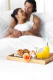 Smiling lovers having breakfast on the bed Royalty Free Stock Image