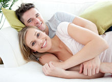 Smiling lovers having fun together on a sofa Stock Images