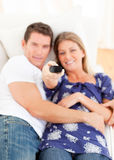 Smiling lovers watching television lying on sofa Royalty Free Stock Photos