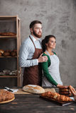 Smiling loving couple bakers standing near bread. Royalty Free Stock Images