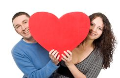 Smiling loving couple holding heart Stock Photos