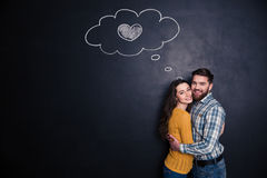 Smiling loving couple hugging over background of chalkboard Royalty Free Stock Photos