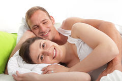 Smiling loving couple lying in bed Royalty Free Stock Photos