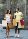 Smiling loving couple with shopping bags at city Stock Photo