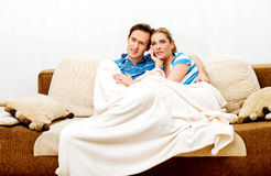 Smiling loving couple sitting on couch with blanket Royalty Free Stock Images
