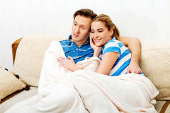 Smiling loving couple sitting on couch with blanket Stock Photos