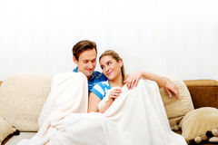 Smiling loving couple sitting on couch with blanket Royalty Free Stock Image