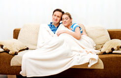 Smiling loving couple sitting on couch with blanket Stock Images