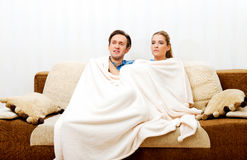 Smiling loving couple sitting on couch with blanket Royalty Free Stock Photography