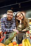 Smiling Loving couple standing near the shopping trolley. With many fruits and looking at the camera Stock Images