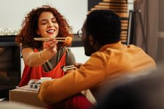 Smiling loving girlfriend sharing her piece of sushi roll with her man royalty free stock images