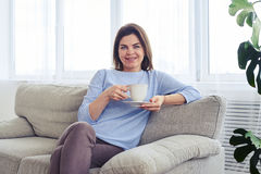 Smiling madam having rest on sofa with cup of coffee Royalty Free Stock Photography