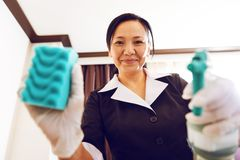 Smiling maid demonstrating her gadgets in work Stock Photos