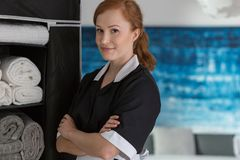 Smiling maid in hotel. Smiling maid in a black and white uniform in a hotel room next to a wardrobe stock images