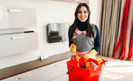 Smiling maid standing against cleaning equipment. Smiling maid in uniform and rubber gloves standing against cleaning equipment, hotel room interior royalty free stock images