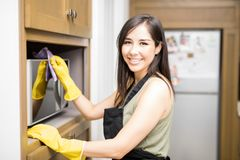 Smiling maid wiping dust on microwave. Elegant young maid wiping outer area of microwave with rug wearing black apron and yellow latex gloves in kitchen Royalty Free Stock Photo