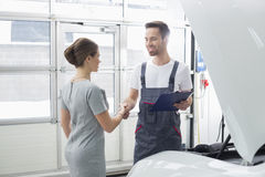 Smiling maintenance engineer shaking hands with female customer in car repair shop Stock Images