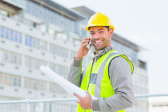 Smiling male architect with blueprints talking on mobile phone Stock Photos