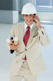 Smiling male architect with hardhat on phone Royalty Free Stock Images