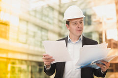 Smiling male architect in helmet with documents Royalty Free Stock Photos